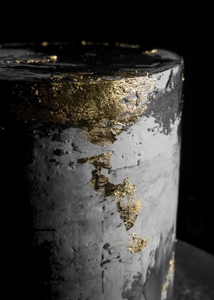 Black concrete gold leaf cake close view