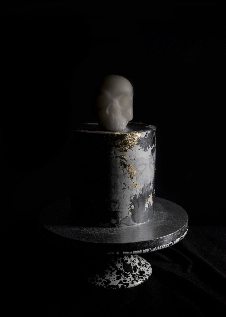 Black concrete gold leaf cake with skull